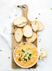 bowl of buffalo chicken dip and crostini for dipping on wood serving platter
