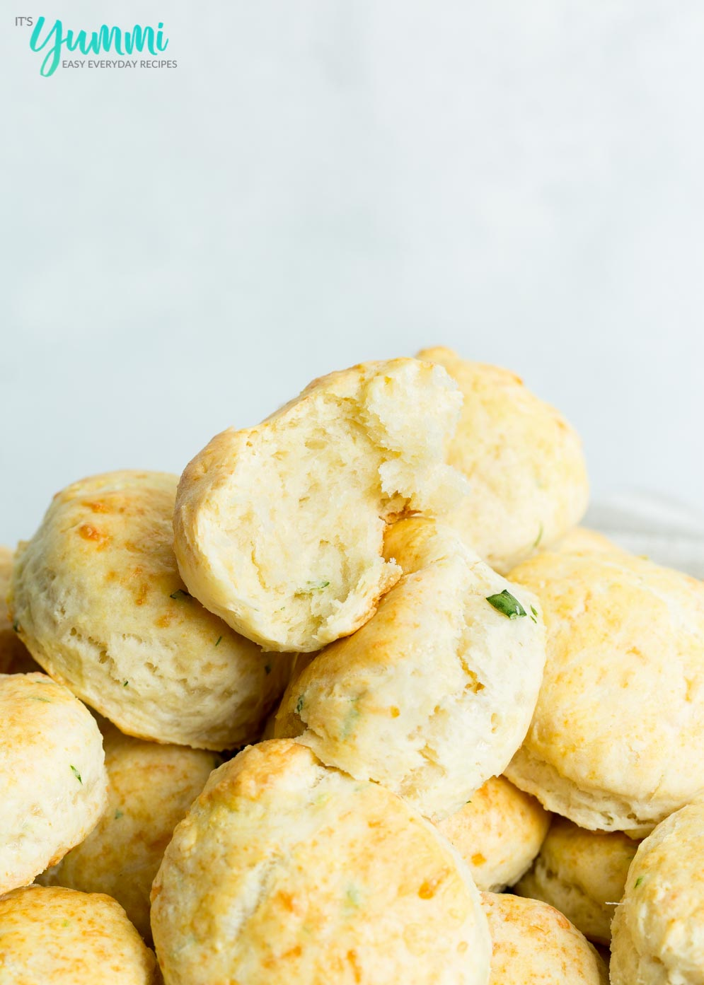Torn in half biscuit on top of fresh biscuits