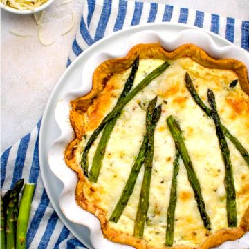 fresh asparagus quiche in white scallop-edge pie dish