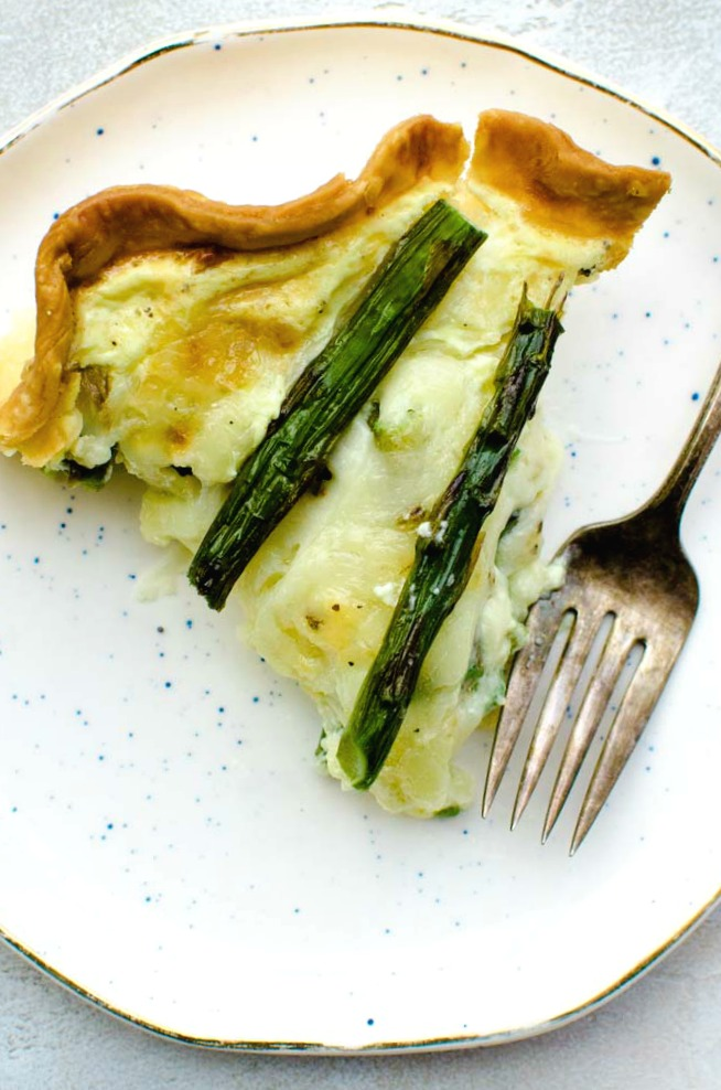 slice of homemade asparagus quiche on small white plate