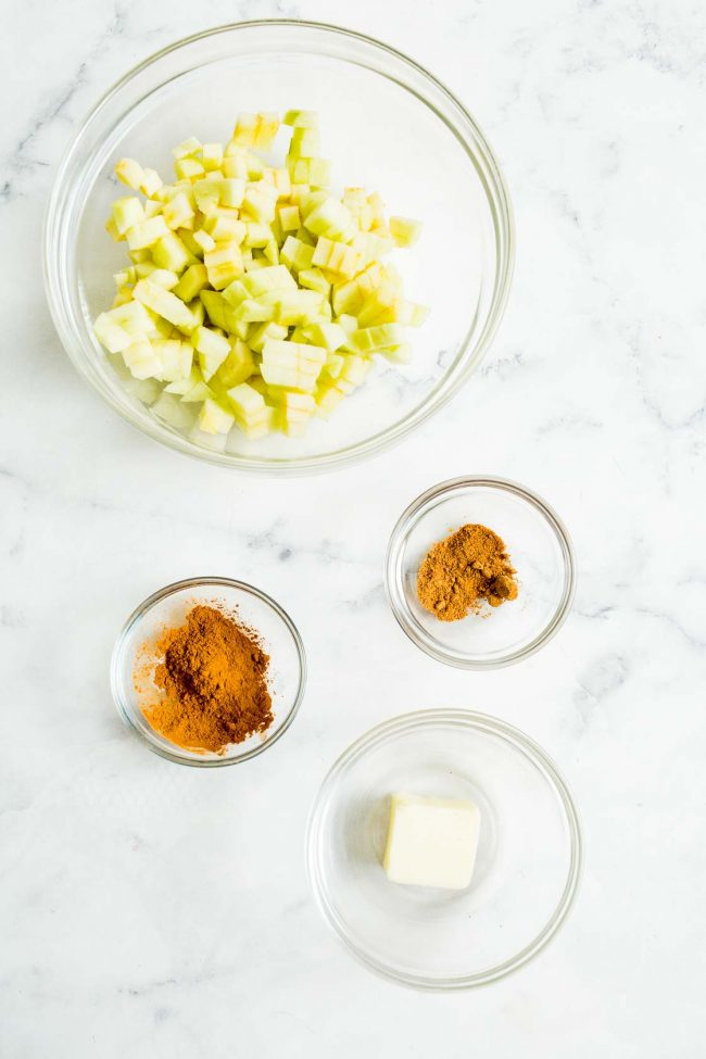 An overhead view of diced apples, cinnamon, nutmeg, and butter.