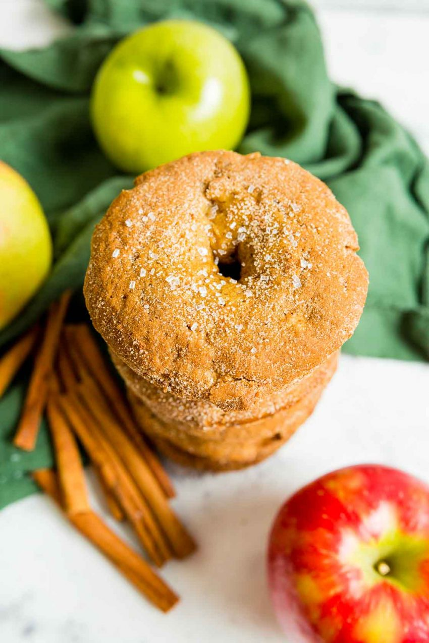 An overhead image of a stack of Apple cinnamon donuts with green and red apples, green napkin and cinnamon sticks in the background.