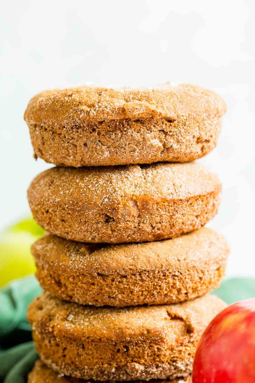 A close up stack of cinnamon apple donuts with cinnamon sugar topping.