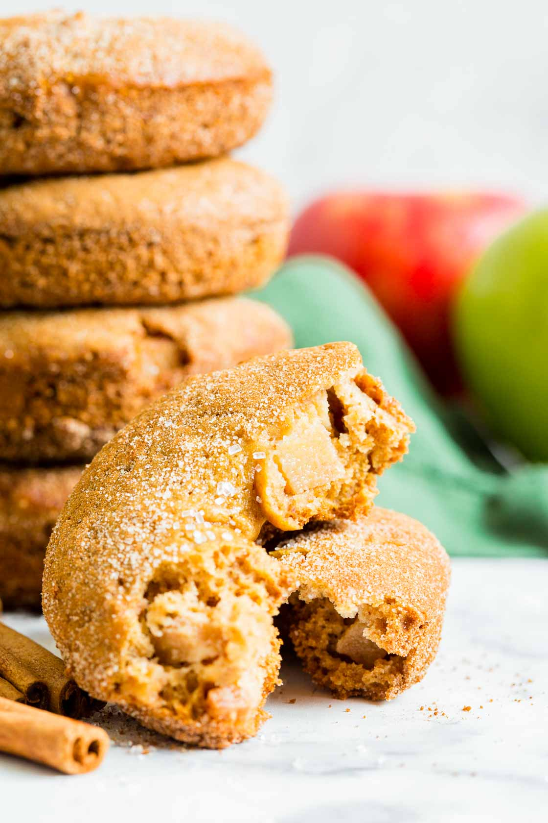 A close up of apple cinnamon donuts broken in half to show apple chunks. A stack of donuts with cinnamon-sugar, a red apple and green cloth in the background.