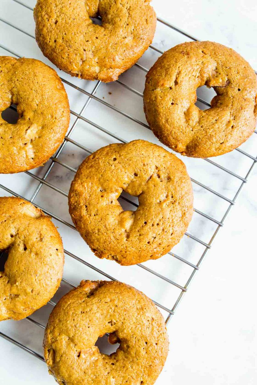 An overhead image of freshly baked apple cinnamon donuts on a cookie sheet.