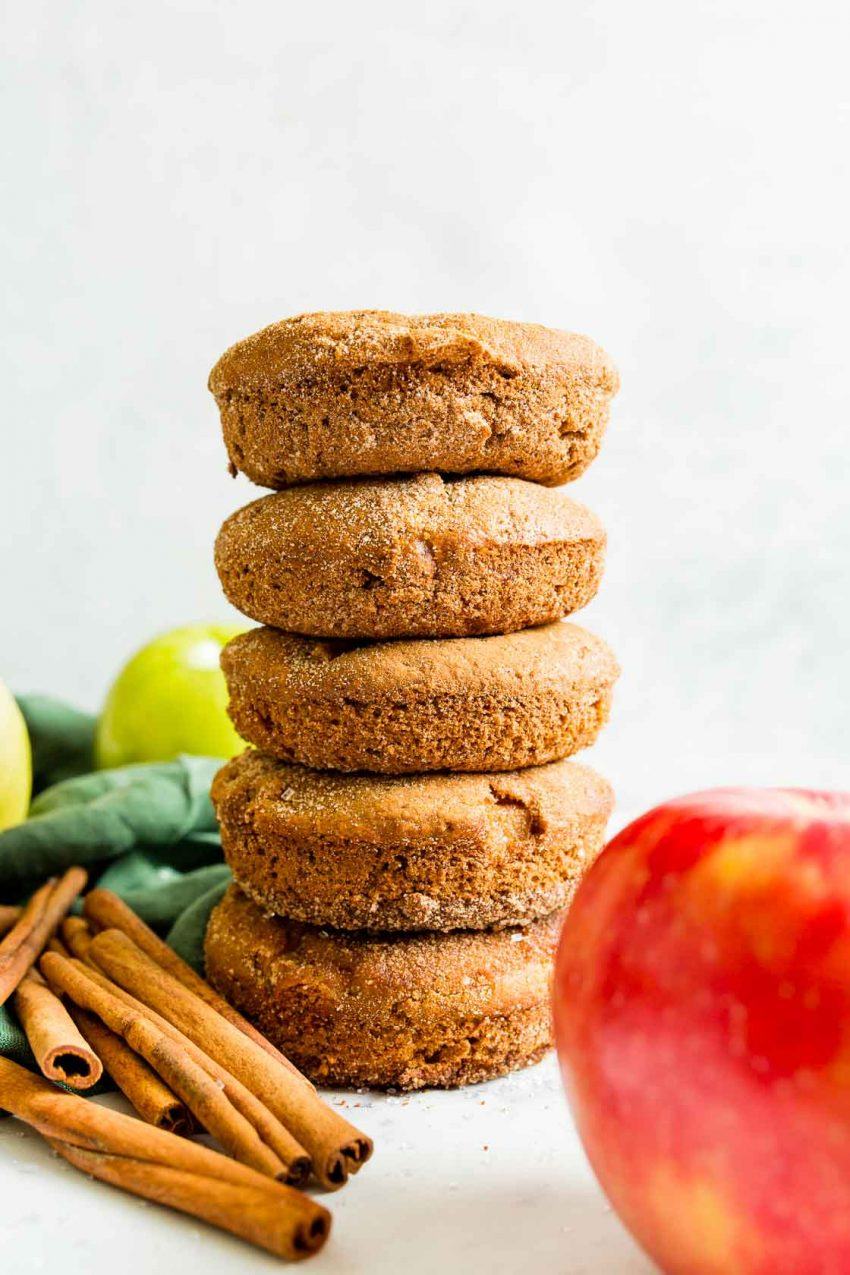 A side view of a stack of five cinnamon sugar coated apple cinnamon donuts.