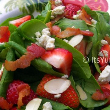 Strawberry Spinach Salad - baby spinach topped with fresh strawberries, crisp bacon, slivered almonds, and crumbled blue cheese. Tossed with a light balsamic vinaigrette dressing.