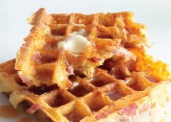 Ham and Cheddar Waffles topped with a pat of butter and maple syrup