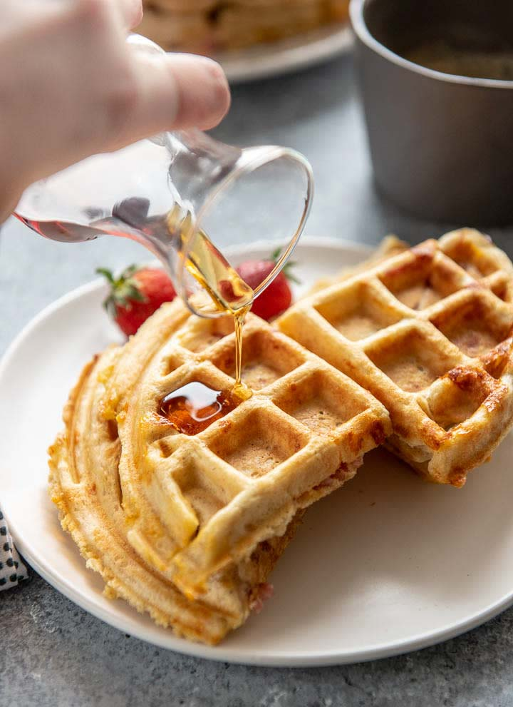 pouring syrup onto homemade ham stuffed waffles