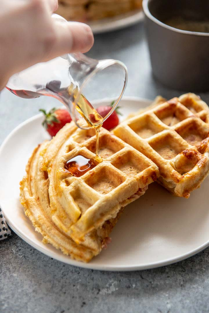 pouring syrup on savory waffles with ham and cheese
