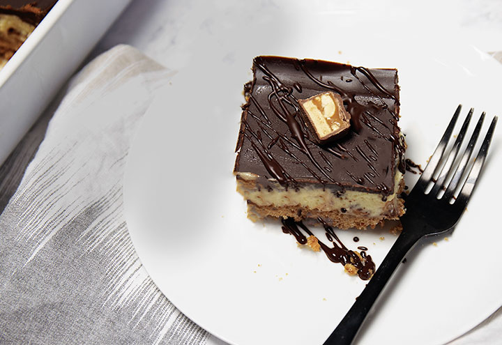 Snickers cheesecake dessert bar on a plate