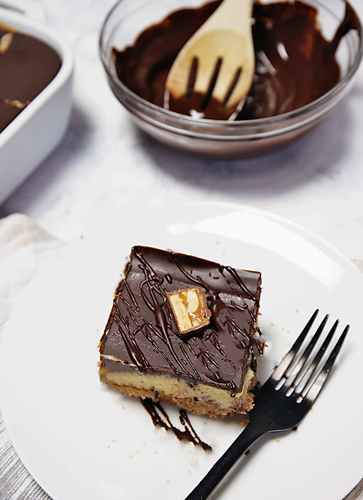 Cheesecake bars with brown butter crust topped with chocolate ganache and Snickers candy bars