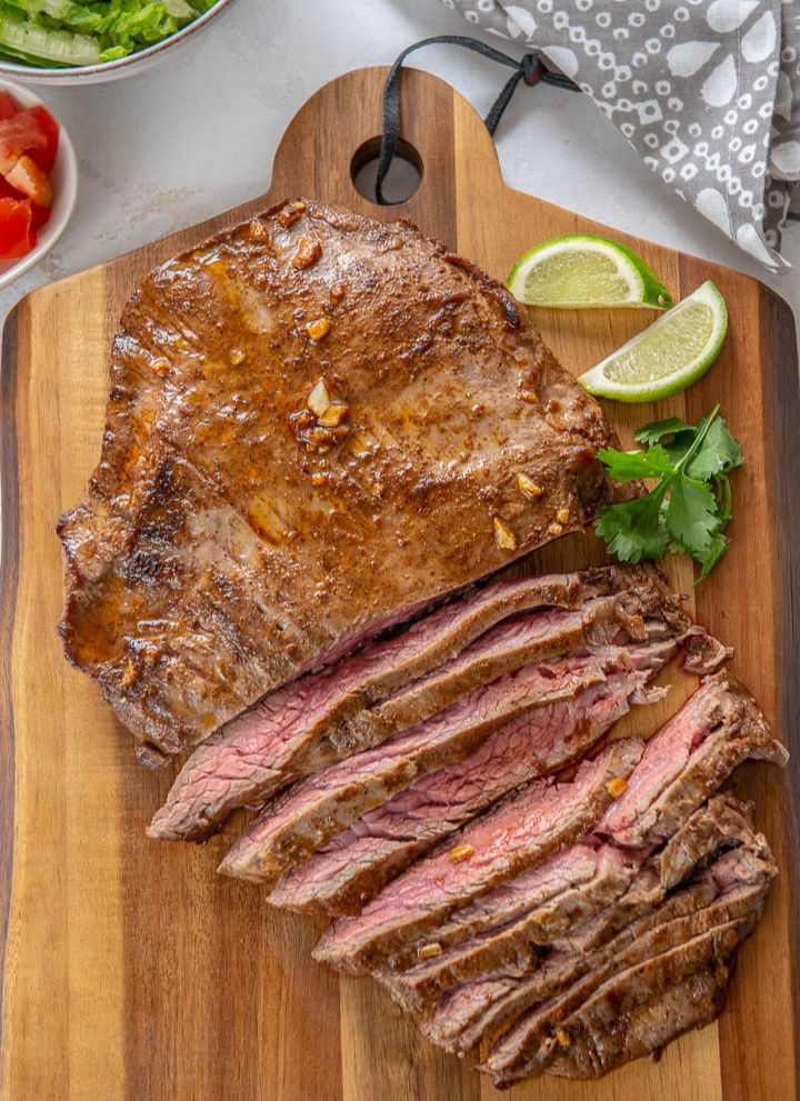 slices of juicy pan seared steak on wooden cutting board