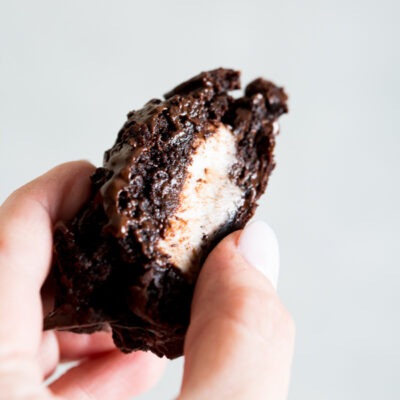 A close up of a single triple chocolate york peppermint patty cookie split in half.