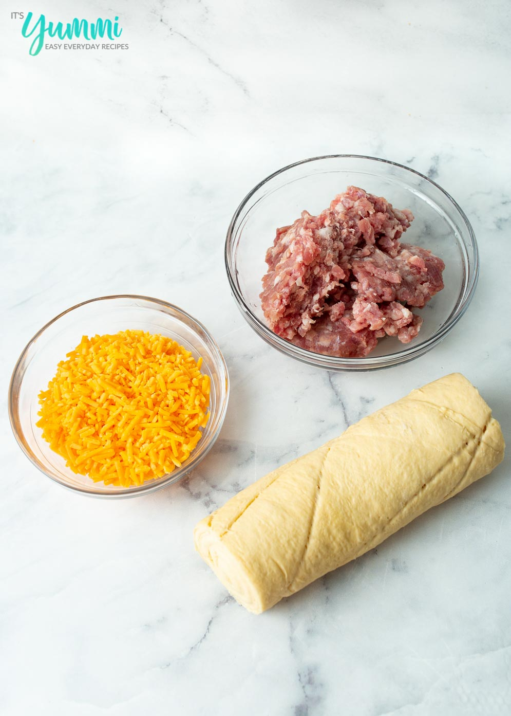 Ingredients for Sausage Biscuits (cheese, sausage and dough)laid out on table