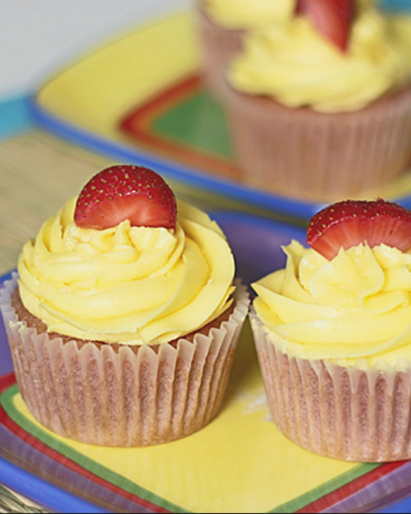 2 strawberry lemonade cupcakes topped with lemon buttercream frosting