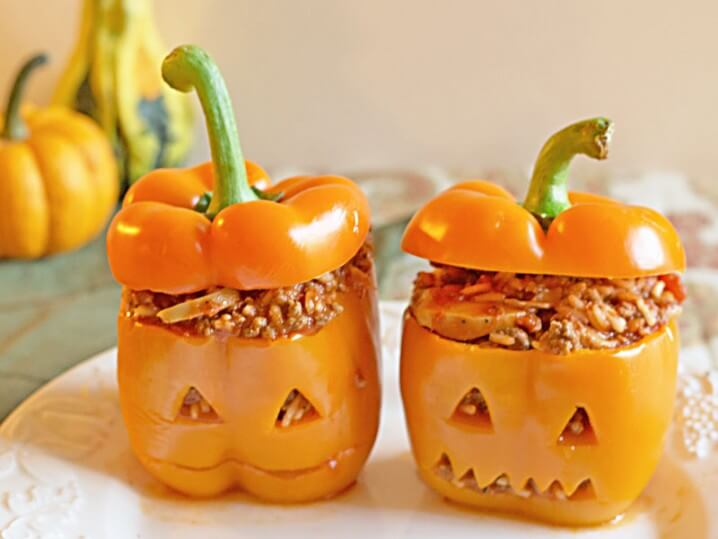 Jack-o-Lantern Halloween Stuffed Bell Peppers - Filled with Italian flavors and a roasted red pepper sauce, this recipe makes a delicious and fun family dinner for Halloween.