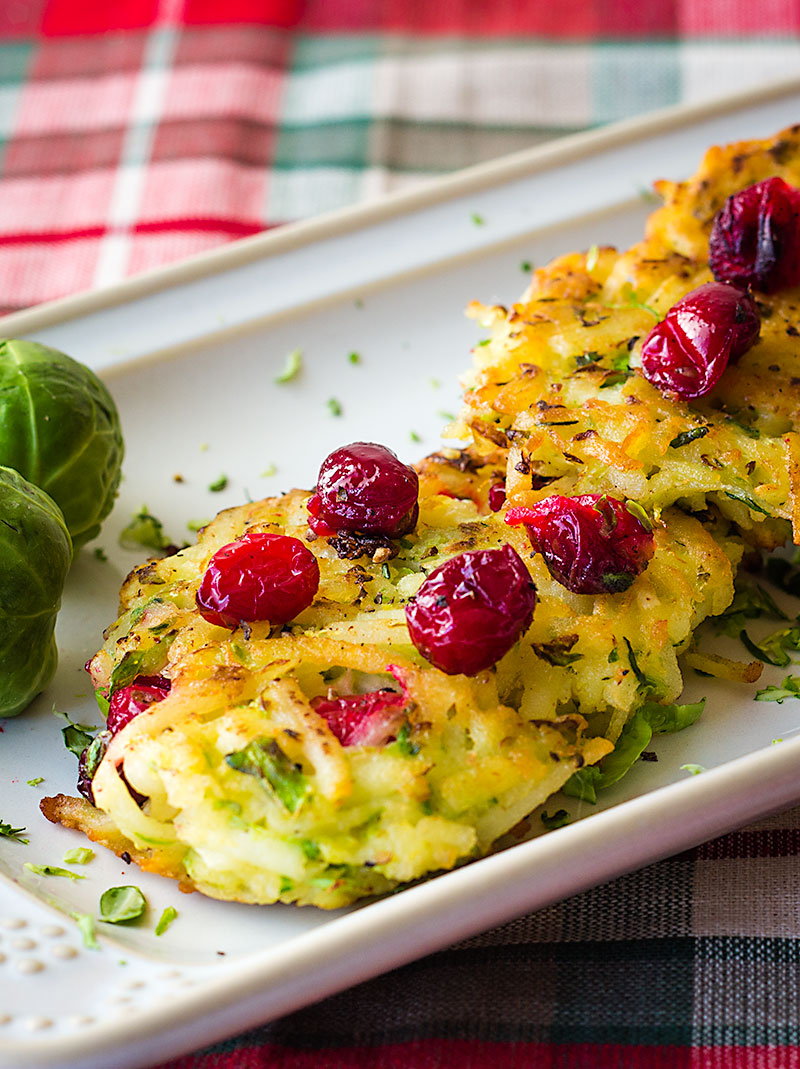 hash brown potato pancakes topped with fresh cranberries and shaved Brussels sprouts