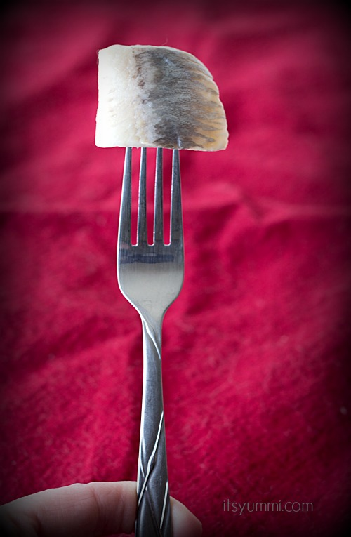 old fashioned pickled herring on a fork
