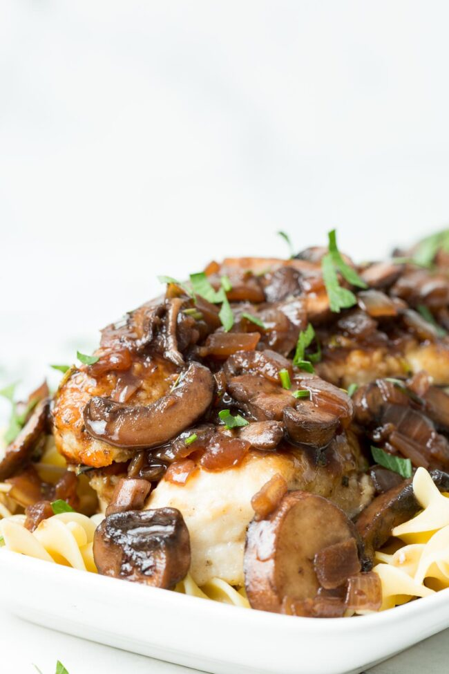 image of a white platter with mushroom chicken bourguignon and fresh parsley
