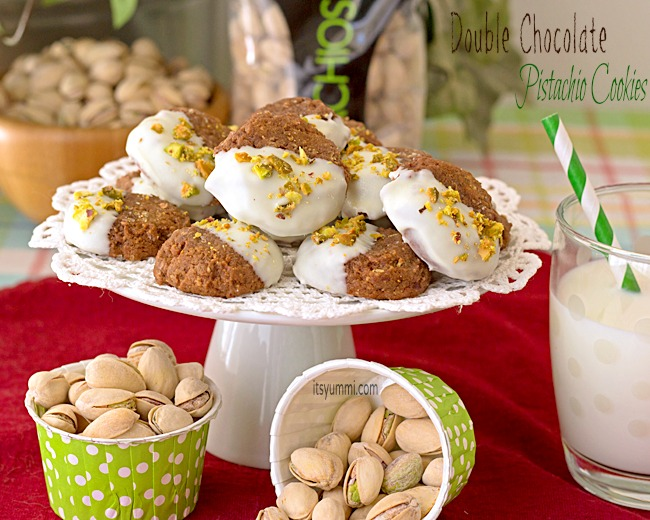 double chocolate pistachio cookies on a cake plate, surrounded by pistachios in the shell