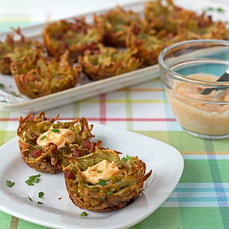 "Easy Cheesy Hash Brown Potatoes ""Bird Nests"" - picture bundles of parslied shredded hash brown potatoes, diced ham, cheese, and seasonings, formed into the shape of bird nests, then baked up until golden brown. Now picture popping them into your mouth with a bit of spicy aioli on the top. Fabulous, right?! Get the recipe from itsyummi.com"