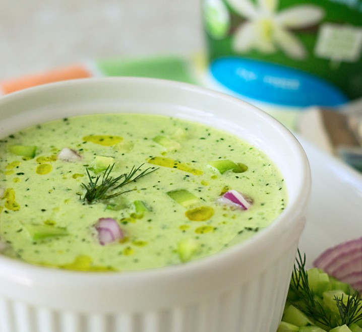 a bowl of cold soup made with cucumbers, Greek yogurt, red onion, fresh dill, tarragon, and parsley