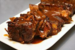 white serving platter full of beef short ribs with a beer bbq sauce