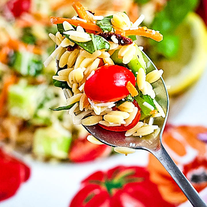 close up shot of orzo salad with garden vegetables on a spoon