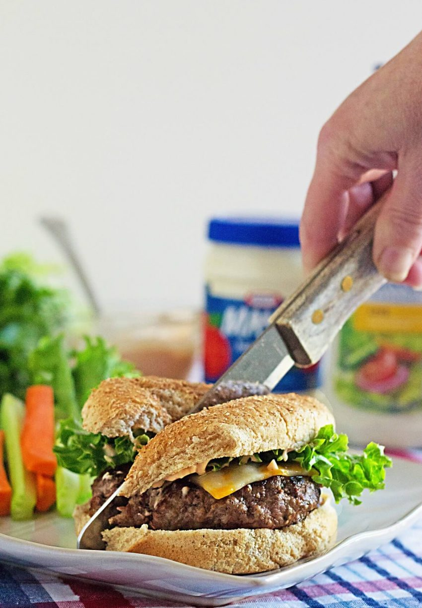 knife cutting a hamburger stuffed with cheese