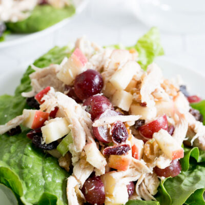 A tabletop view of chicken waldorf salad on a white plate with lettuce and glass of water