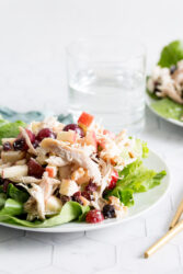 A tabletop view of chicken waldorf salad on a white plate with lettuce. A blue cloth napkin, glass of water, and gold untensils