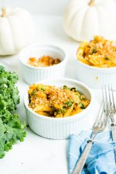 creamy turkey pumpkin pasta in white bowls set next to kale and white pumpkins