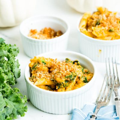 creamy turkey pumpkin pasta in white bowls set next to kale and white pumpkins