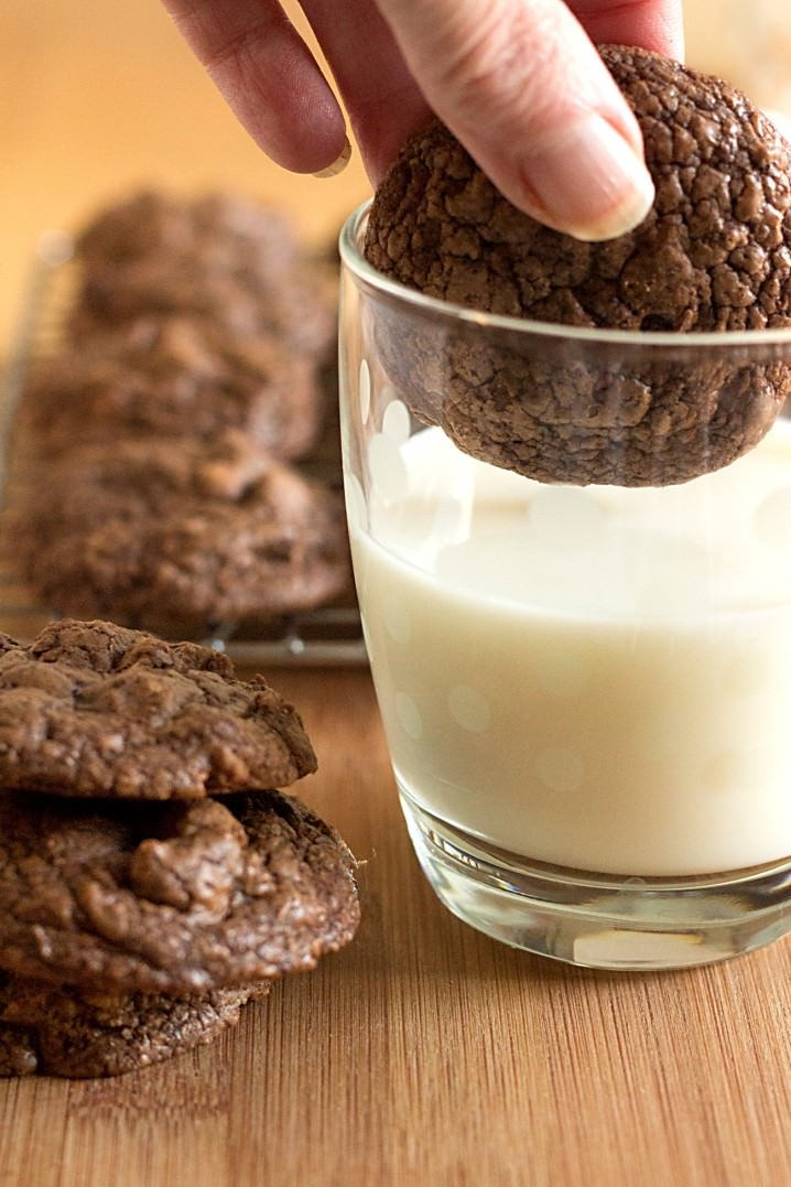 soft chocolate cookie being dunked into glass of milk