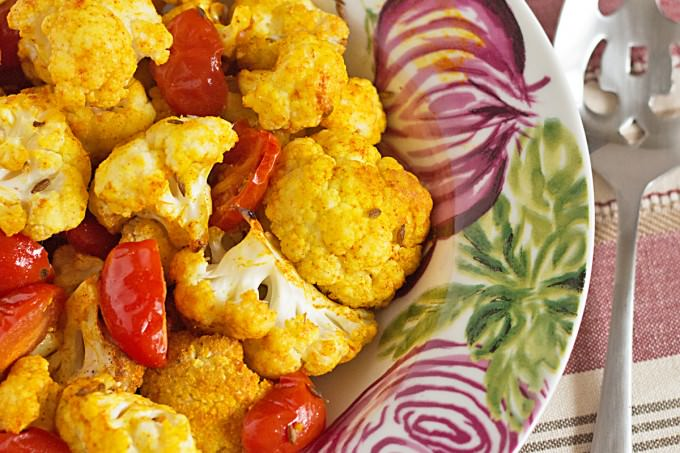 Indian Spiced Roasted Vegetables recipe - cauliflower, grape tomatoes and white cannellini beans are seasoned with tumeric, sweet paprika, and cumin. A great vegetarian dish for meatless Monday or as a side with chicken or lamb!