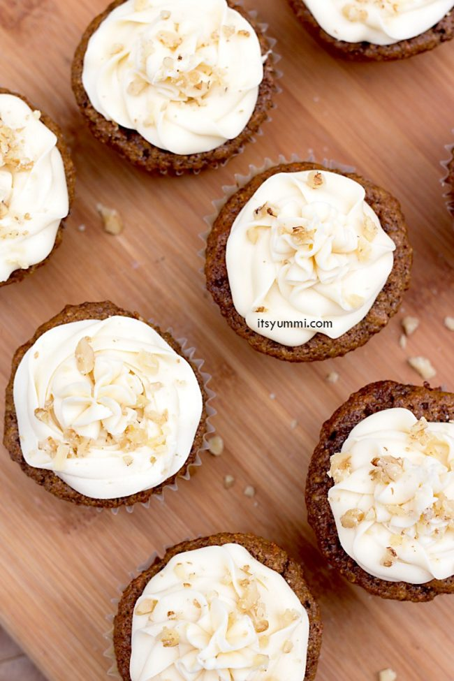 carrot cake cupcakes topped with cream cheese frosting, sitting on a wood platter