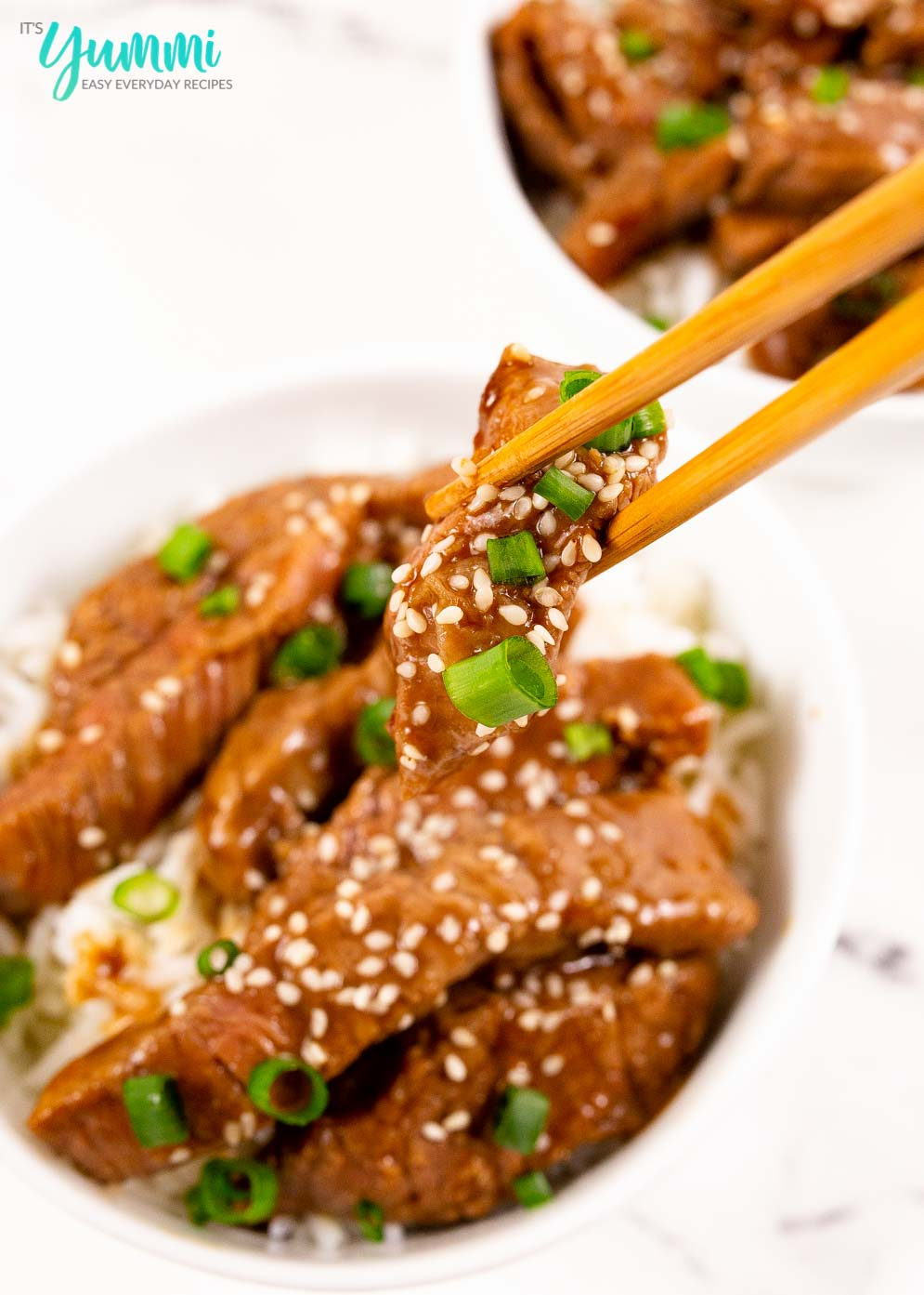 Close-up shot of chopsticks holding a piece of pf changs mongolian beef strip with scallions and sesame seeds on top