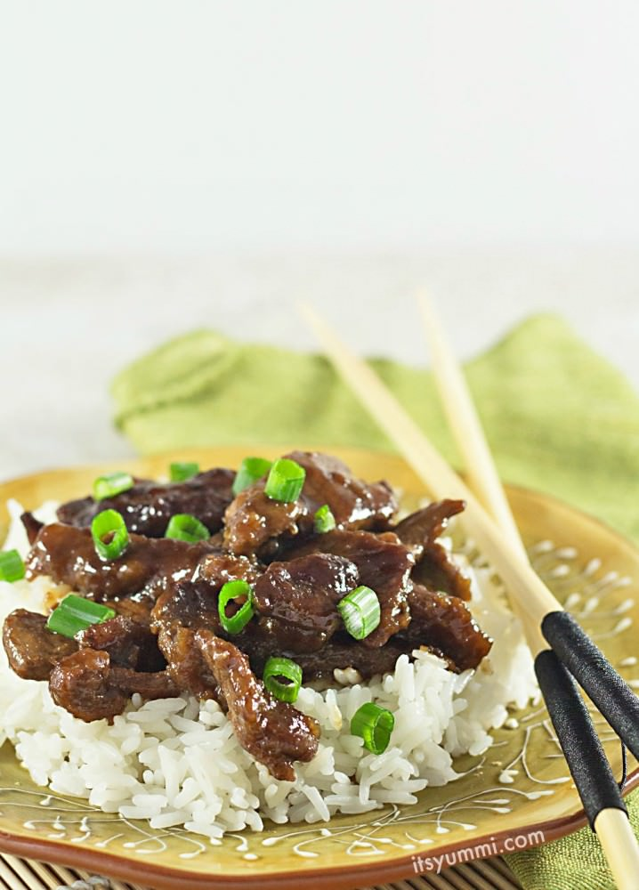 dinner plate of copycat PF Chang's Mongolian beef on a bed of fluffy white rice. Chopsticks on the plate.