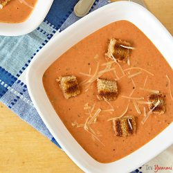 a bowl of creamy tomato soup with grilled cheese croutons
