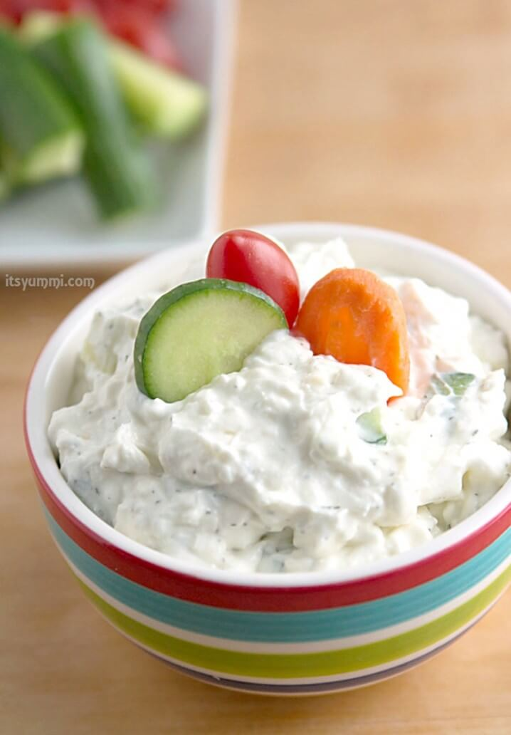 bowl of creamy dill cucumber yogurt dip with fresh raw veggies dipped into it.