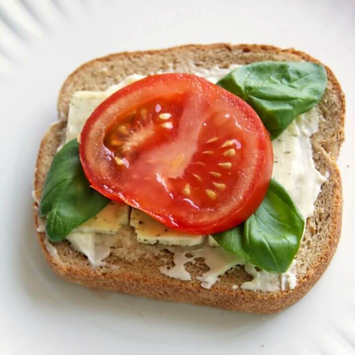 Basil, tomato, and cheese on a slice of Pepperidge Farm<sup>®</sup> Harvest Blends bread.