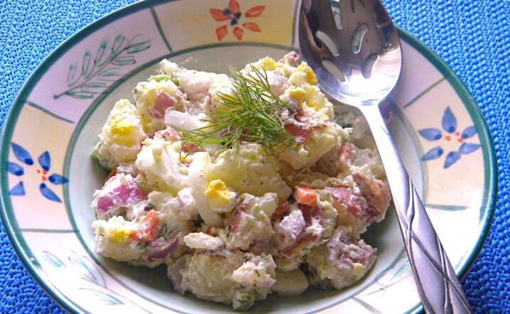 bowl of Farmer's Market Potato Salad with a serving spoon on the side of the bowl