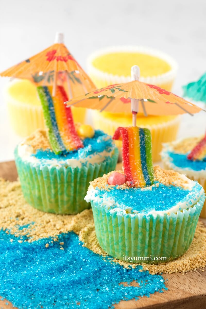 Day at the Beach Cupcakes - an easy cupcake idea using lemon cupcakes. Cupcakes decorated with candy, cookie crumbs, and colored sugar to look like a day at the beach.