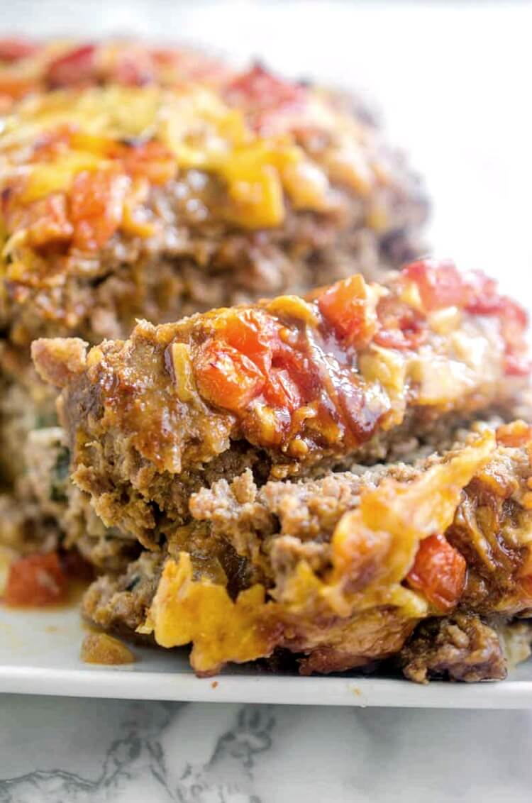 Veggie stuffed meatloaf is the best meatloaf I've ever eaten - complete comfort food. Ground pork and beef meatloaf is stuffed with spinach, onions, and cheese, then topped with barbecue sauce, tomatoes, and more cheese! #meatloaf #recipe #dinner
