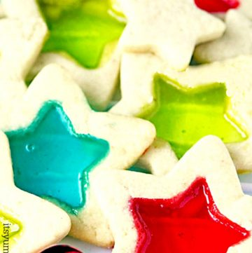 Stained Glass Christmas Cookies are beautiful, delicious, and easy to make Christmas cookies.  This Christmas cookie recipe starts with soft butter cookie dough, rolled out and cut into holiday shapes, then filled with melted candies so the center looks like stained glass.  #christmas #cookies