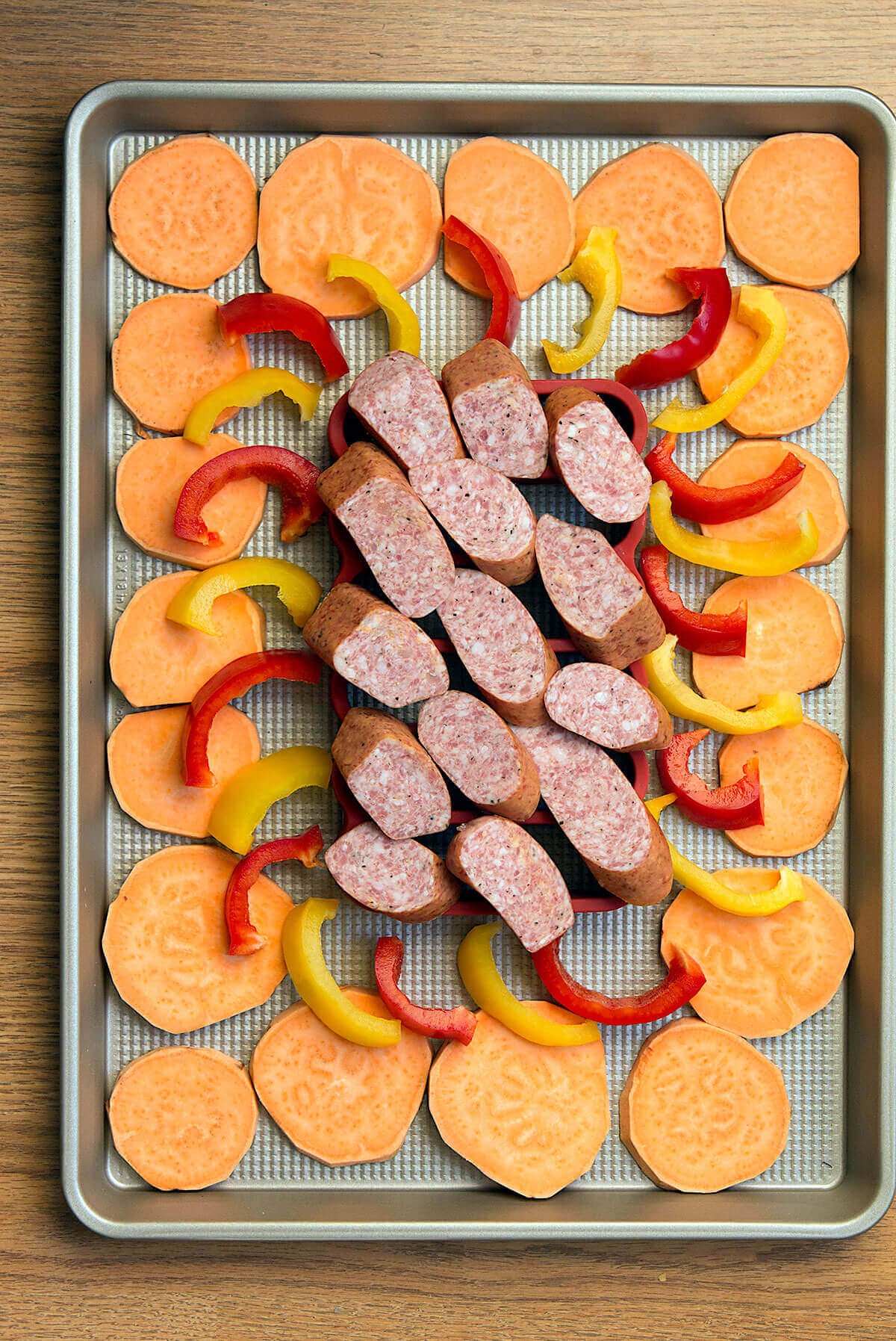 This easy sausage sheet pan dinner is a delicious and quick weeknight meal! Smoked sausage, sweet potatoes, and bell peppers are lightly seasoned, then roasted for 20 minutes in this one pan dinner recipe.