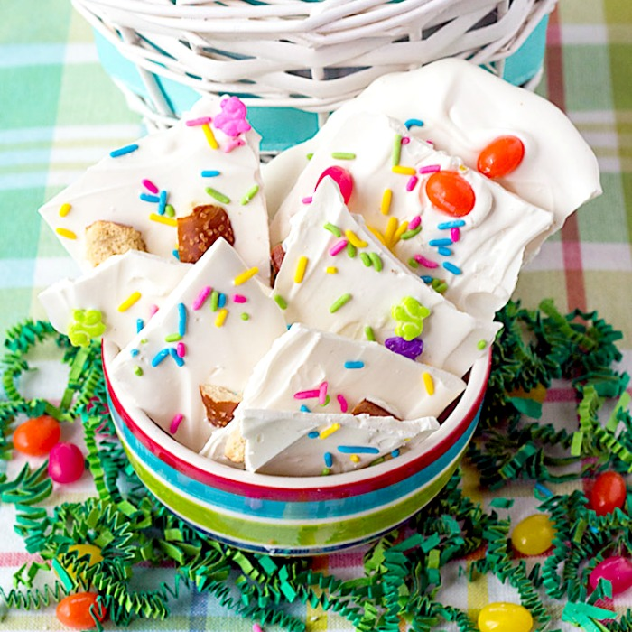 a bowl of white chocolate homemade Easter treats - bark covered with broken Dutch pretzels, pastel colored sprinkles and jelly beans