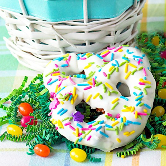 homemade white chocolate covered pretzels with Easter sprinkles and some jelly beans sitting on Easter grass in front of a white Easter basket
