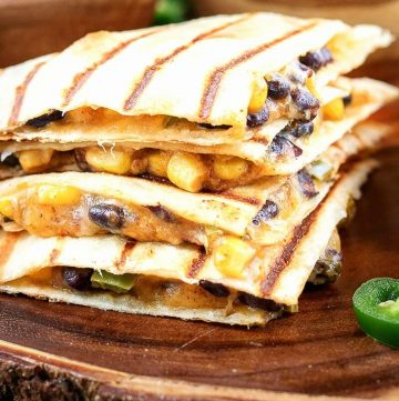 Corn and Black Bean Vegetarian Quesadillas stacked onto a natural wood platter